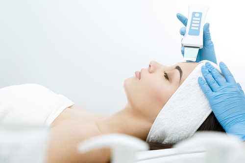 Doctor with Ultrasonic scraber. Doing procedure of ultrasonic cleaning of face. Model_ profile. Cosmetological clinic. Patient. Healthcare_ clinic_ cosmetology