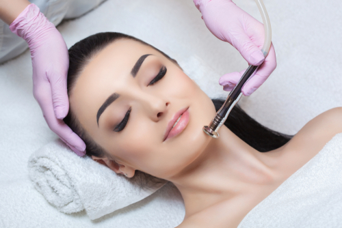 The cosmetologist makes the procedure Microdermabrasion of the facial skin of a beautiful_ young woman in a beauty salon.Cosmetology and professional skin care.