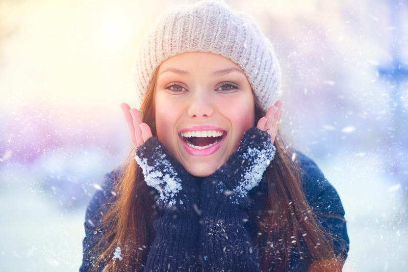 Winter young woman portrait. Beauty Joyful  Model Girl touching her face skin and laughing, having fun in winter park. Beautiful young woman laughing outdoors. Enjoying nature, wintertime