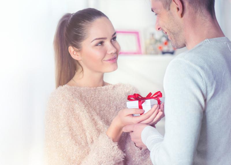 Valentines Day Gift. Young Couple holding gift and smiling. St. Valentine s Day_ Love concept. Hands in Hands_ romance_ dating concept.Beautiful young man giving a Gift to his Girlfriend.