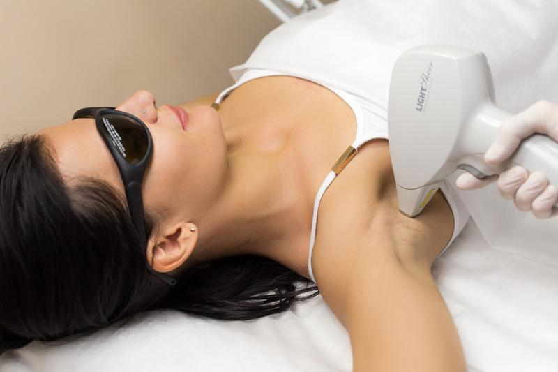 Laser hair removal in professional beauty studio. Beautician in white sterile gloves make the procedure on the client s armpit.