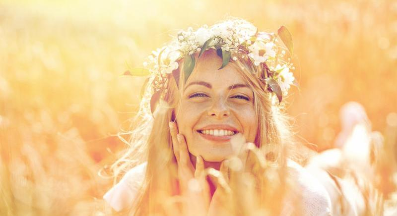 nature_ summer holidays_ vacation and people concept - face of happy smiling woman or teenage girl n in wreath of flowers on cereal field
