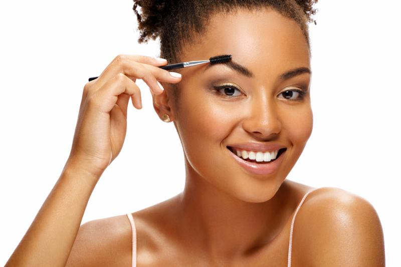 Smiling girl using brush for eyebrows. Photo of young african american girl on white background. Youth and Beauty