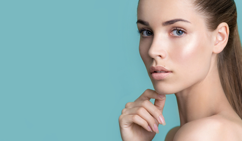 Beautiful young woman with clean perfect skin. Portrait of beauty model with natural nude make up and touching her face. Spa_ skincare and wellness. Close up_ blue background_ copyspace.