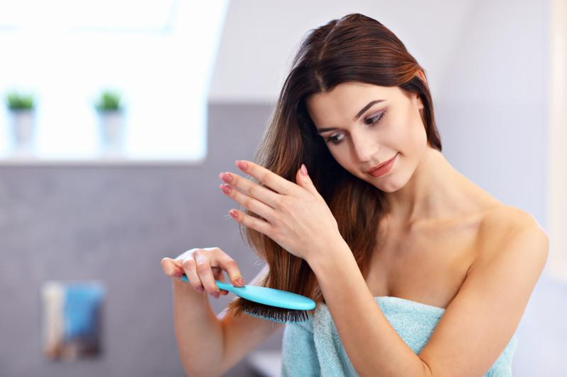 young woman taking care of hair in bathroom