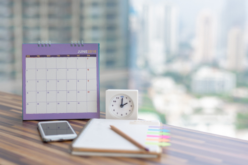 Open Notebook Calendar June 2018 with smartphone diary clock pencil blurred background modern office. Event organizer midyear half year planning_ timetable_ schedule. Calendar 2018 Concept.