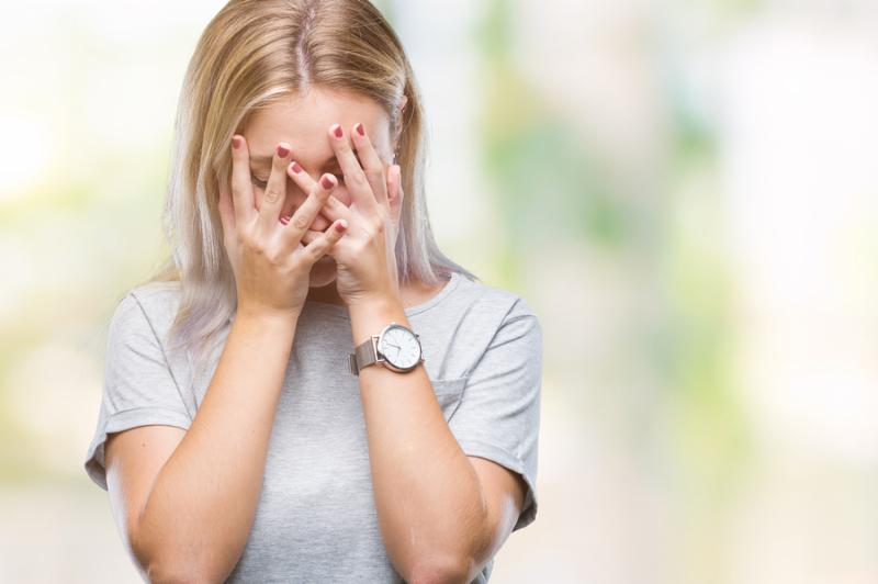Young blonde woman over isolated background with sad expression covering face with hands while crying. Depression concept.