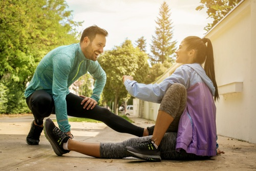 Couple stretching after workout . She sitting on the sidewalk.  Healthy lifestyle.