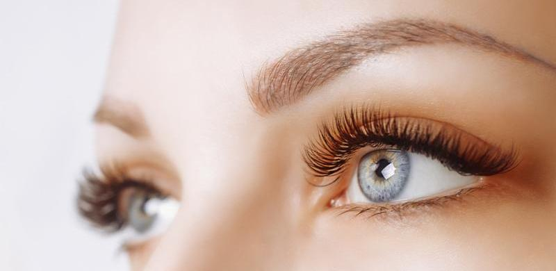 Eyelash Extension Procedure. Woman Eye with Long Eyelashes. Lashes. Close up_ macro_ selective focus