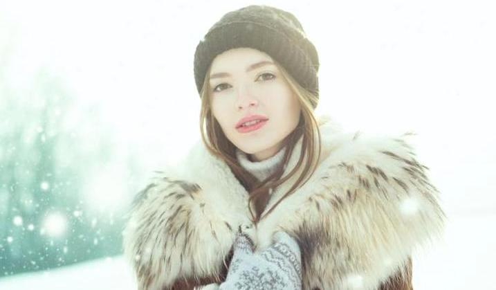 Young woman at winter. Portrait of a happy teenage girl in the snow