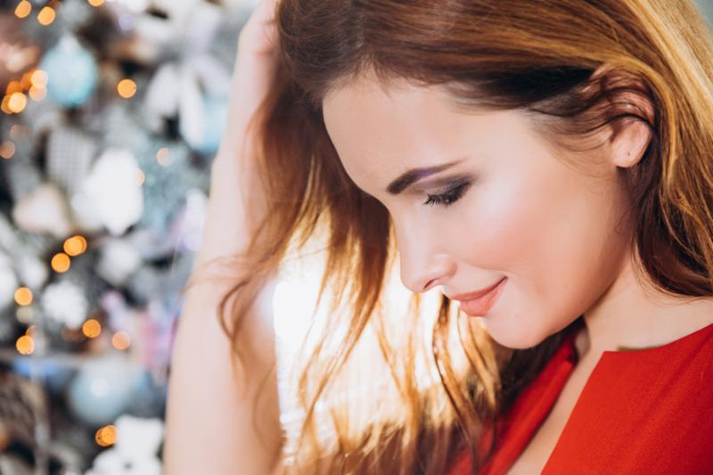 Christmas. Beautiful smiling woman Elegant over christmas tree in red dress lights background. happy new year.