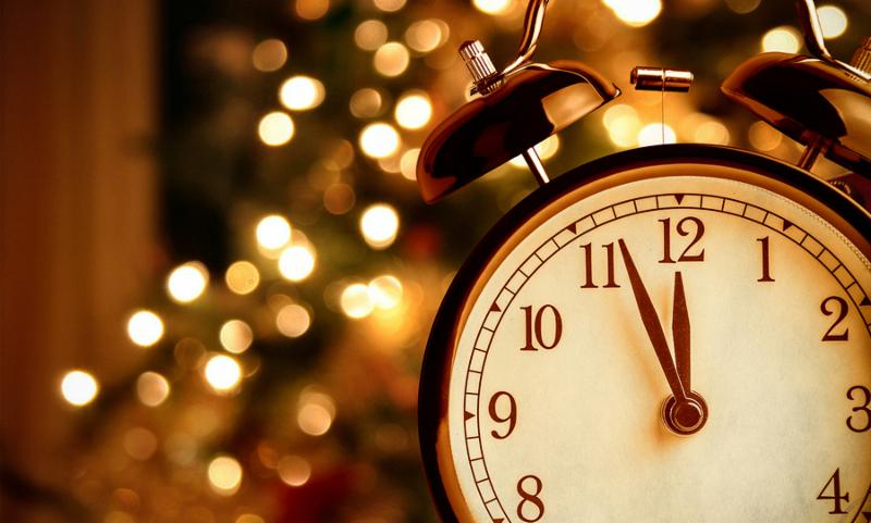 vintage alarm clock is showing midnight. It is twelve o clock christmas and bokeh holiday happy new year festive concept on light tree background
