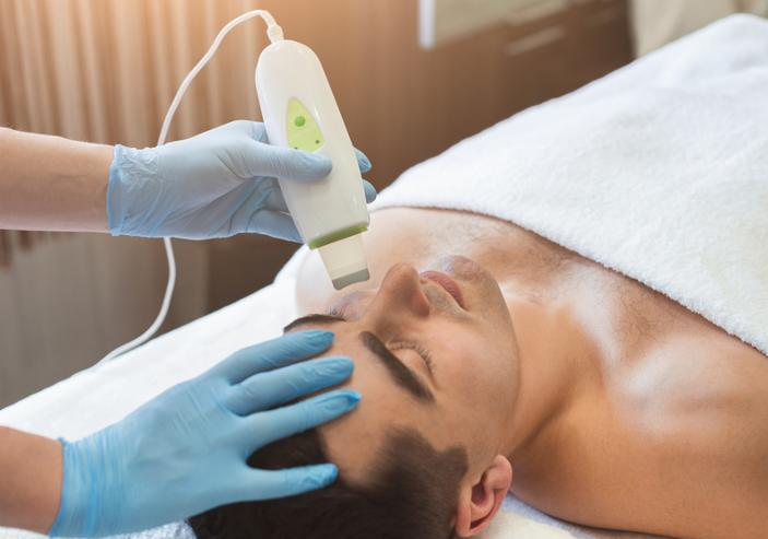 Rejuvenating facial treatment. Man getting lifting therapy massage in a beauty SPA salon. Exfoliation_ stimulation and hydratation. Aesthetic cosmetology_ closeup_ copy space