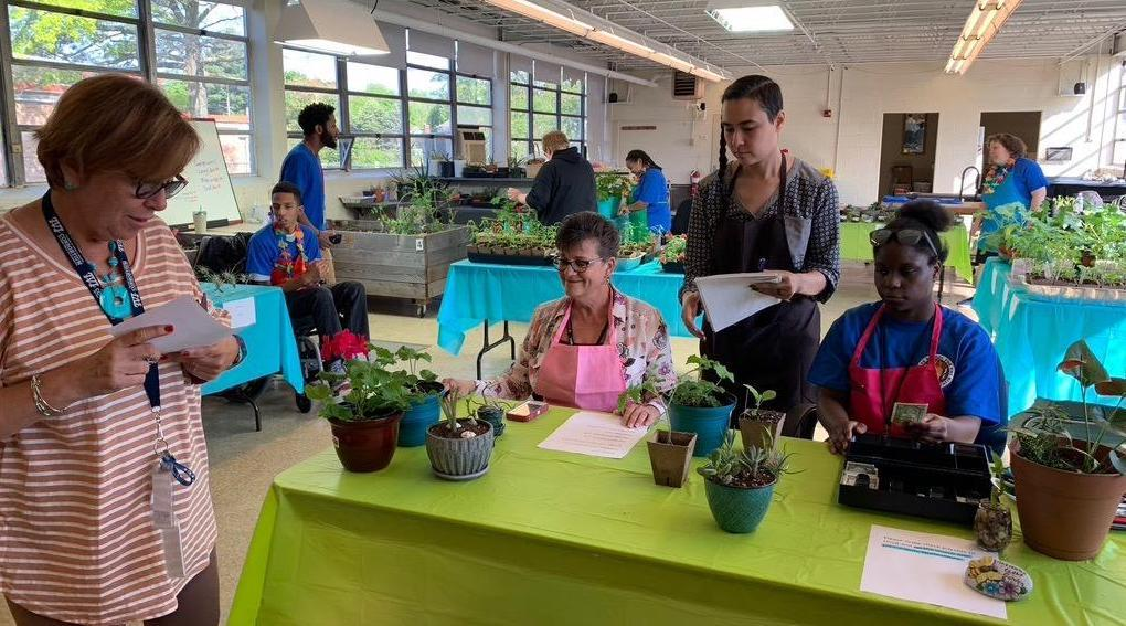 students and volunteers working to transplant plants into pots