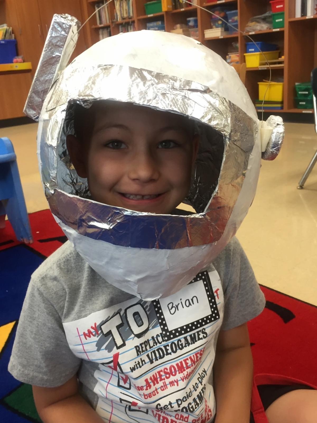 A little boy smiling in an astronaut helmet.