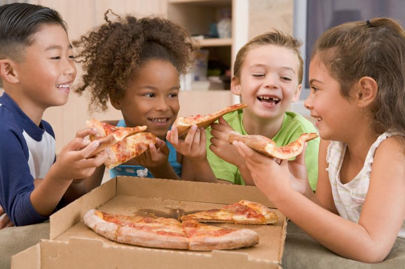 Portrait of young children eating pizza