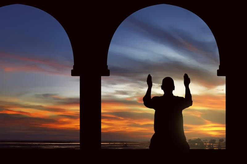 Image of silhouette man praying with mosque background