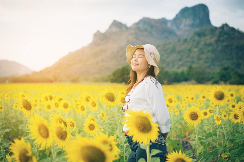 Happy woman in sunflower field smiling with happiness due to healthy food. Happy people health care and agriculture business concept. Happy farmer or farm worker in sunny day at sunflower field.