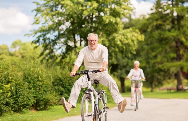 active old age_ people and lifestyle concept - happy senior couple riding bicycles at summer park