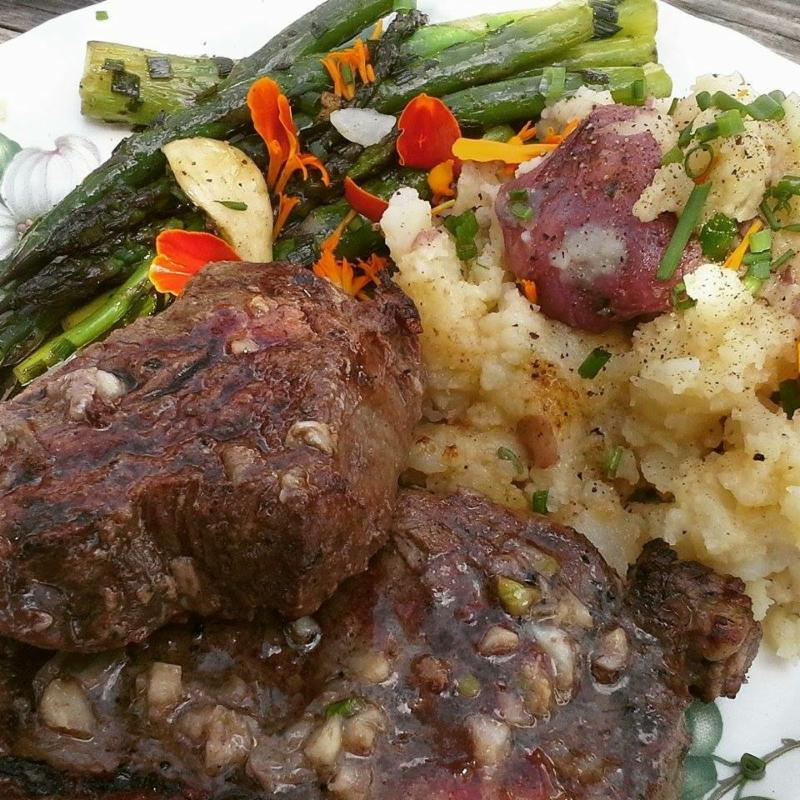 Grilled grass fed steak with smashed potatoes and asparagus, sprinkled with fresh herbs.