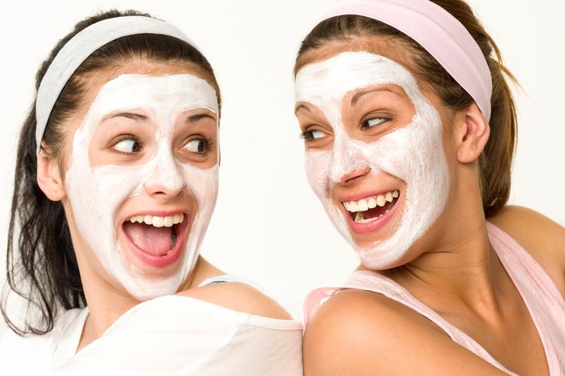 Cheerful girls having facial mask and laughing at each other