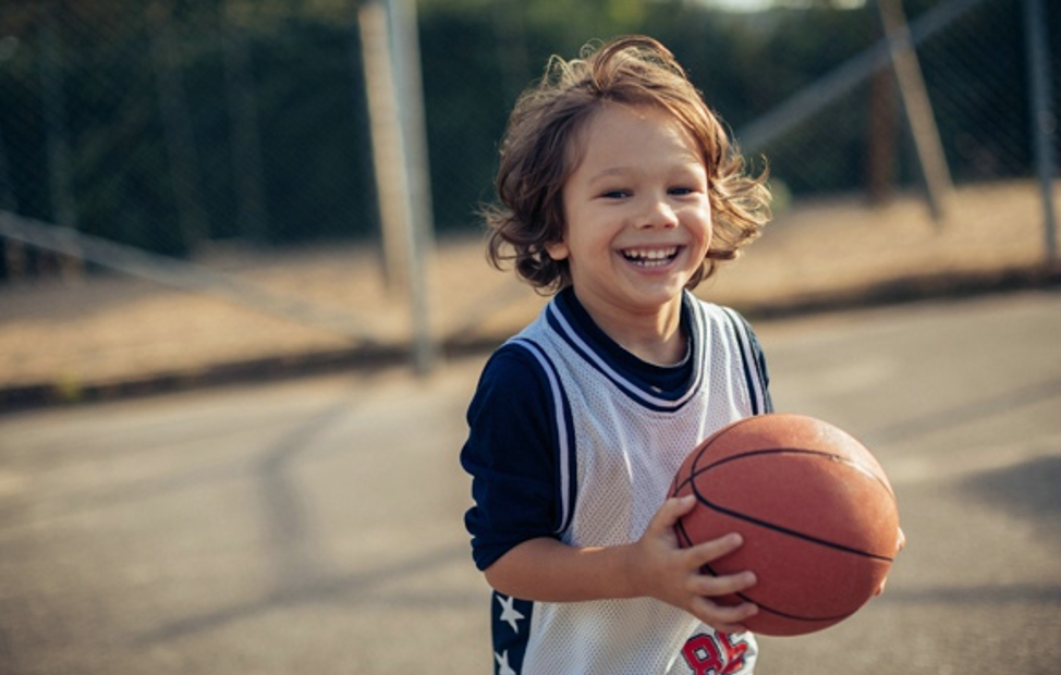 a young boy smiling and holding a basketball