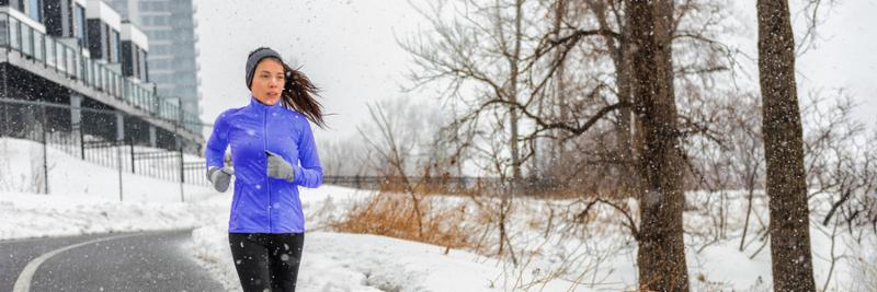 Winter running Asian girl wearing winter run jacket training cardio outside in snowflakes snow fall during cold day outdoors in city street. Fitness woman doing workout outside. Panoramic banner.