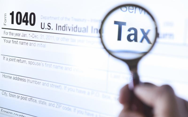 Hand holding a magnifying glass with tax form 1040 in background