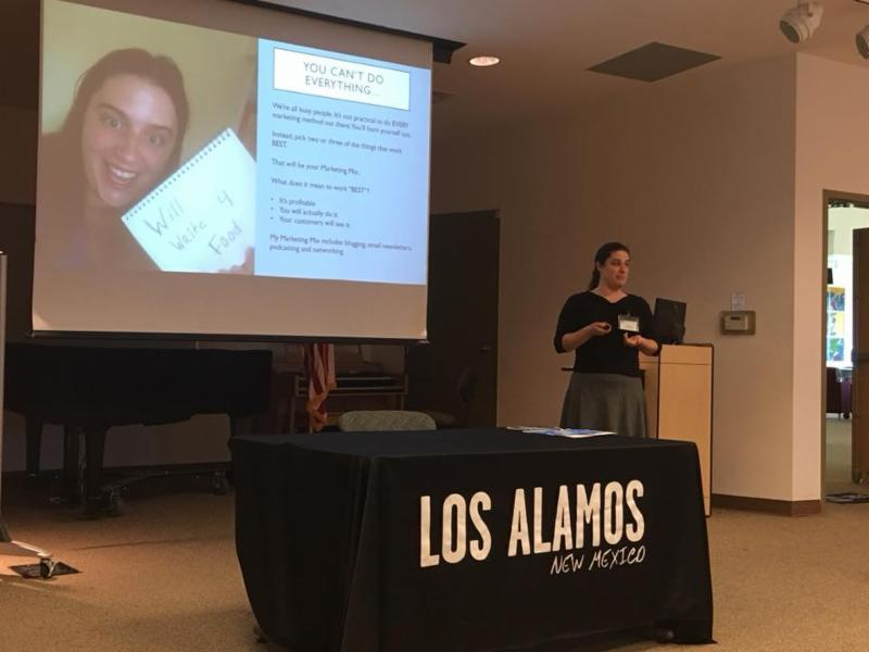 Mandy Marksteiner speaking in front of a projection screen and table with a cloth emblazoned: Los Alamos, New Mexico.