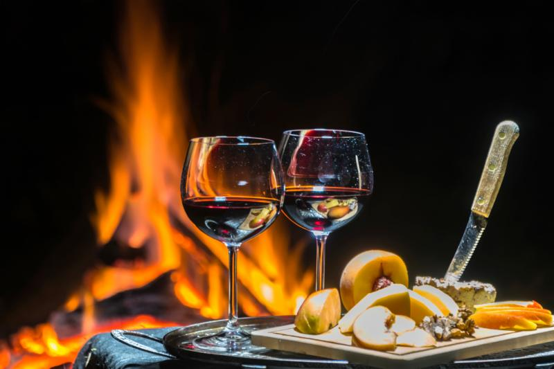 fruit and cheese spread with wine next to a campfire