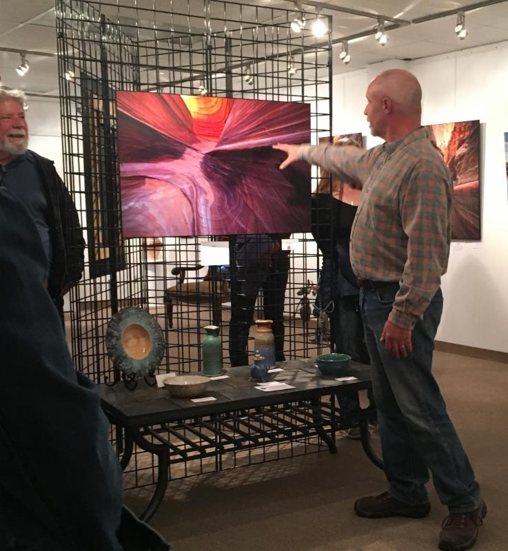 man pointing at a painting on a pop-up gallery, while other patrons look on