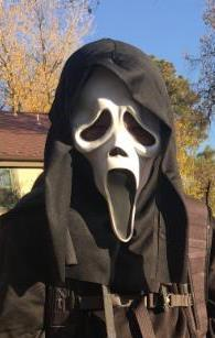 person in a neighborhood wearing a Ghostface mask and cloak