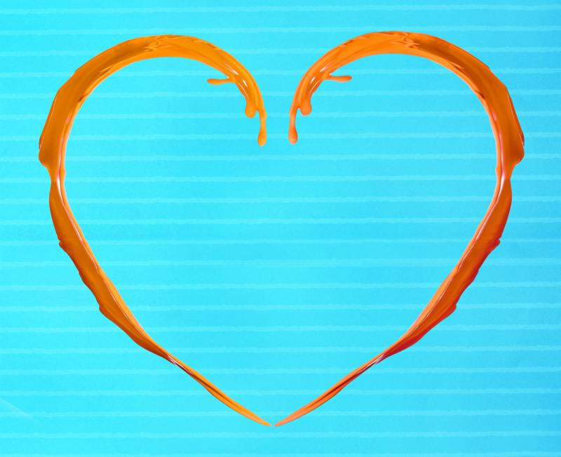 Orange heart made of paint splash on blue background