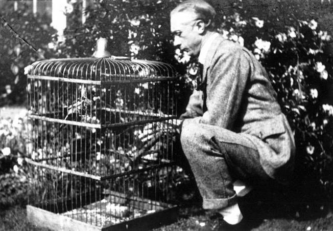 Photo copyright 2010 The Society of Teachers of the Alexander TechniqueF.M. Alexander squats down to reach and hold bird in cage on the ground. bird in