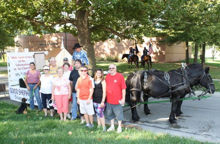church members and parade float on horse-drawn wagon