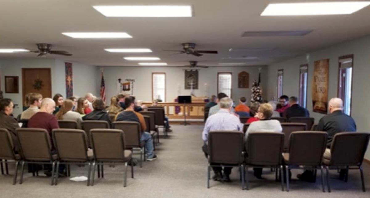 interior of new building in Waukon showing worshippers in chairs and front of church