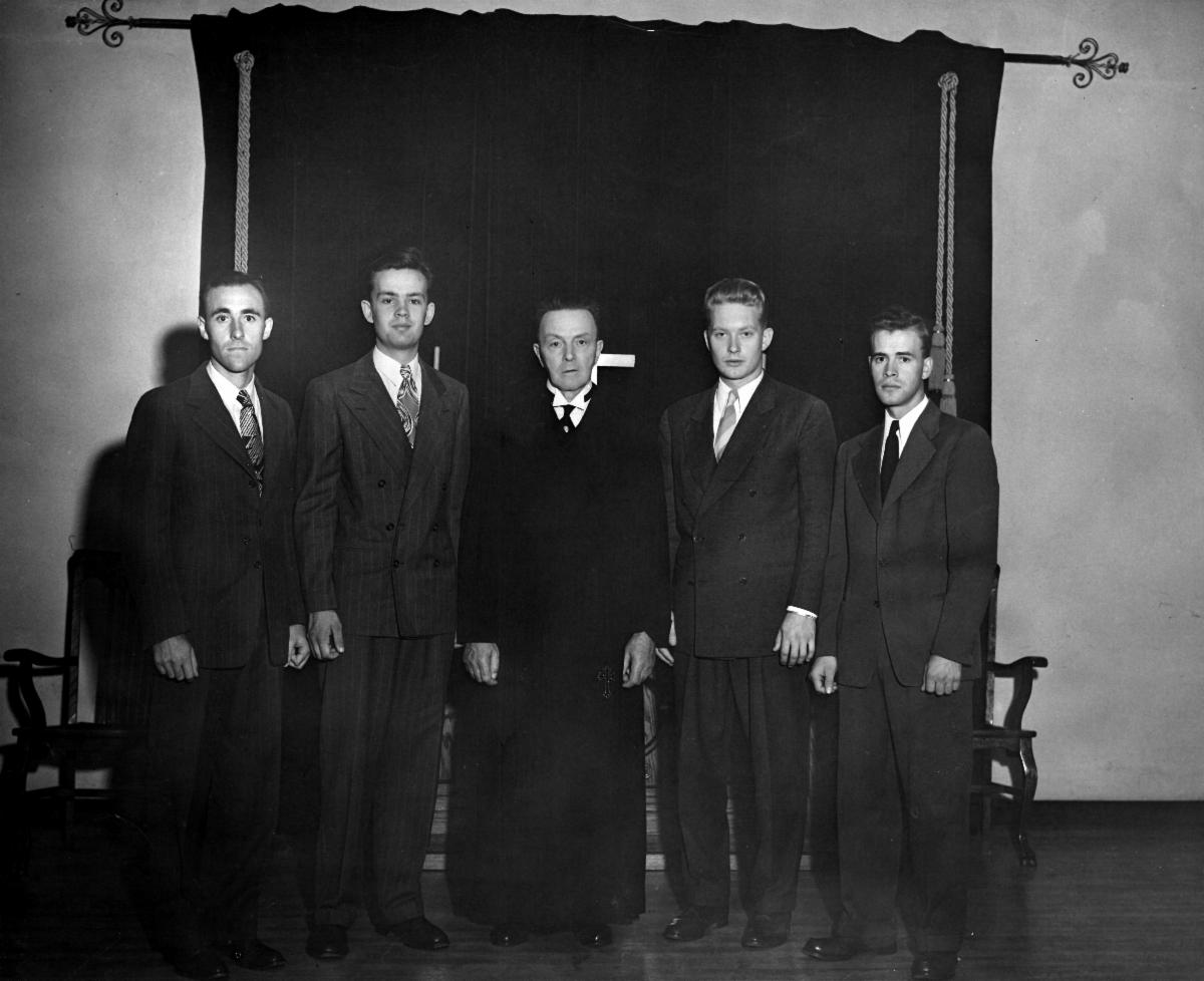 black and white photo of five men standing in front of cross and curtain