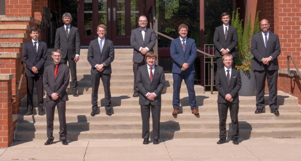 ten seminary students outside spaced apart on steps