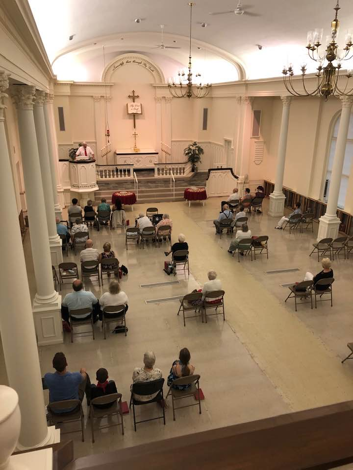 view from balcony of church with pastor in the pulpit and individuals seated in spaced folding chairs
