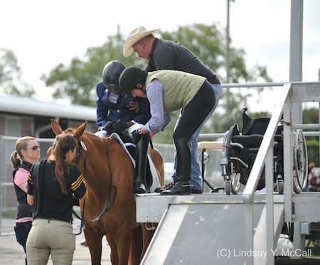 U.S. Air Force Veteran Derrick Perkins uses the mounting ramp provided by Vinceremos Therapeutic Riding Center at the 2015 Adequan Global Dressage Festival CPEDI3* January in Wellington, FL. Photo (C) Lindsay Y. McCall