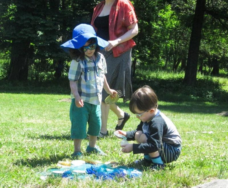 "Two children, one standing, the other kneeling, playing with pieces of ""sea glass"" strewn on the lawn"