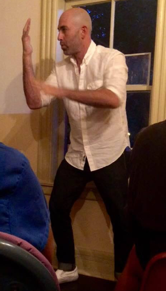 Bald man in white shirt stands in front of window making gestures with his hands