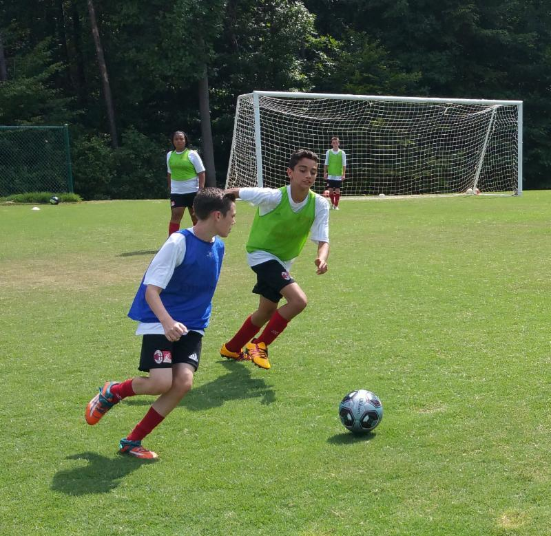 Two boys vie for the ball in front of a soccer goal