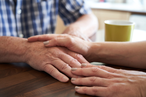 Close Up Of Woman Comforting Unhappy Senior Man Sitting In Kitchen At Home