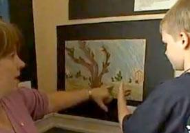 Boy showing artwork to teacher.
