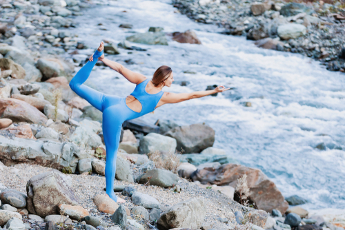 Adorable positive female yoga instructor doing virabhadrasana pose while standing against of wild river in mountains while traveling through reserved places. Concept of health and unity with nature