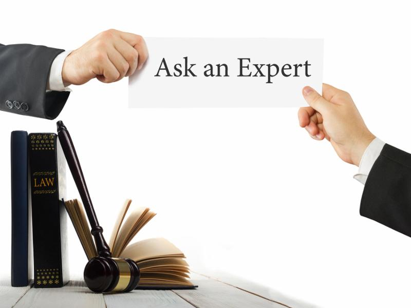 Law book and wooden judges gavel on table in a courtroom or law enforcement office. Lawyer Hands holding business card with text Ask an Expert.