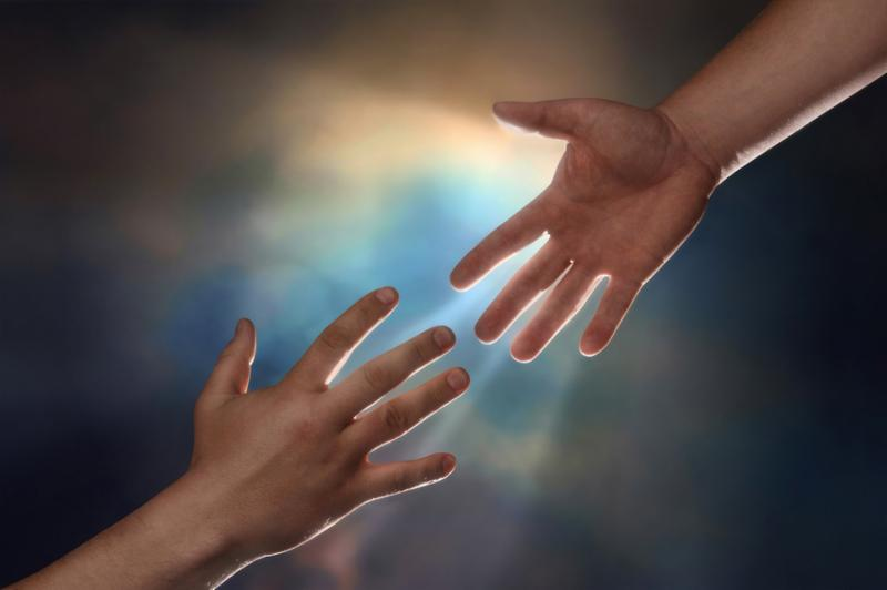 Two male hands one reaching down to assist another hand reaching up with sunburst in the background