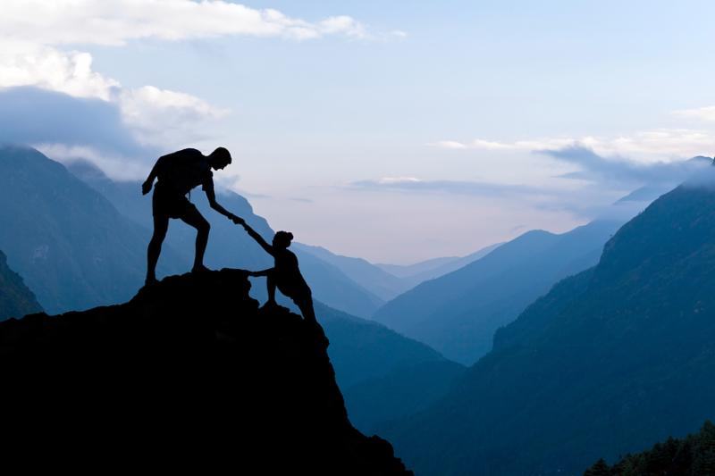 Teamwork couple helping hand trust assistance silhouette in mountains sunset. Team of climbers man and woman hiker help each other on top of mountain climbing assistance beautiful sunset landscape in Himalayas Nepal