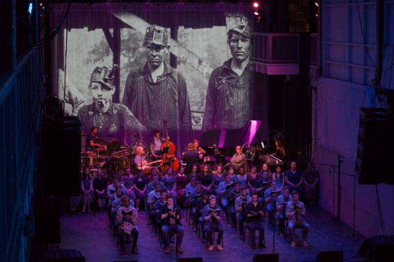 A choir is seated in chairs bathed in a blue-red light in front of a black and white projection of coal miners.